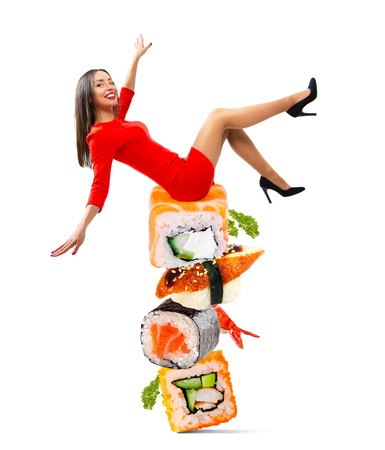 Young beautiful woman sitting on a mountain of sushi Stock Photo