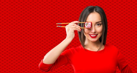 Young woman holding sushi with a chopsticks, isolated on red Reklamní fotografie