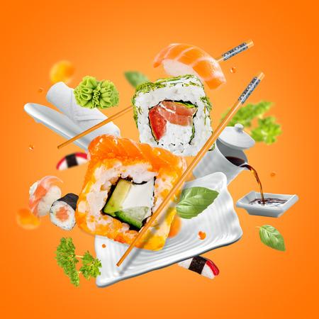 Delicious pieces of sushi, isolated on orange background