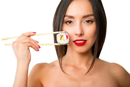 Young woman holding sushi with a chopsticks, isolated on white