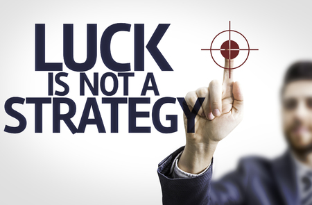 business management: Business man pointing to transparent board with text: Luck is Not a Strategy