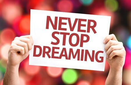 card stop: Never Stop Dreaming card with colorful background with defocused lights Stock Photo