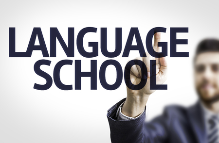 Business man pointing to transparent board with text: Language School Stock Photo