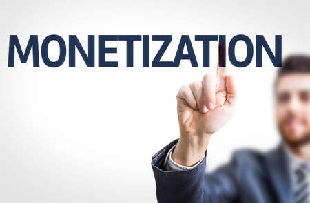 monetizing: Business man pointing to transparent board with text: Monetization
