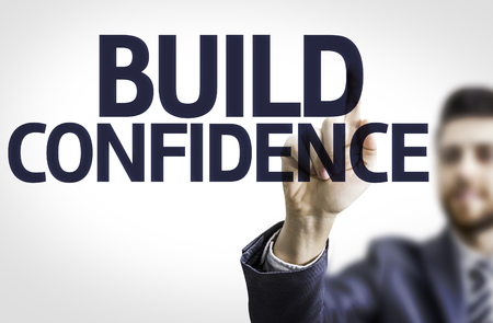 self assurance: Business man pointing to transparent board with text: Build Confidence Stock Photo