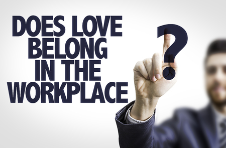 belong: Business man pointing to transparent board with text: Does Love Belong in the Workplace?