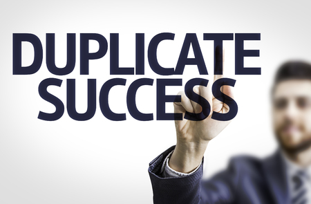 emulate: Business man pointing to transparent board with text: Duplicate Success