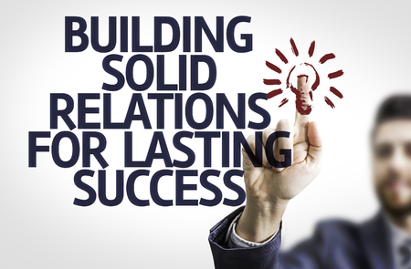 business support: Business man pointing to transparent board with text: Building Solid Relations For Lasting Success