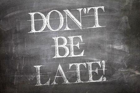 llegar tarde: No llegar tarde por escrito en la pizarra Foto de archivo