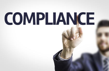 comply: Business man pointing to transparent board with text: Compliance