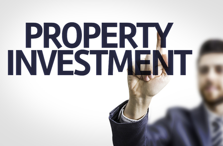 press agent: Business man pointing to transparent board with text: Property Investment