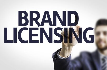 licensing: Business man pointing to transparent board with text: Brand Licensing