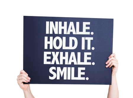 exhale: Hands holding Inhale Hold It Exhale Smile card isolated on white Stock Photo