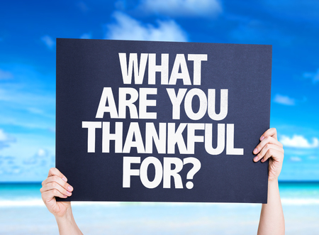 thankfulness: Hands holding What Are You Thankful For? card with beach background