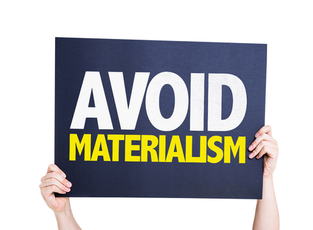 materialism: Hands holding Avoid Materialism card isolated on white background Stock Photo