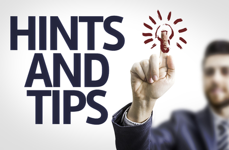 hints: Business man pointing to transparent board with text: Hints and Tips