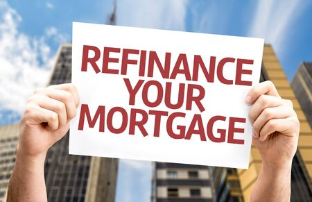 refinance: Hands holding Refinance Your Mortgage card with urban background