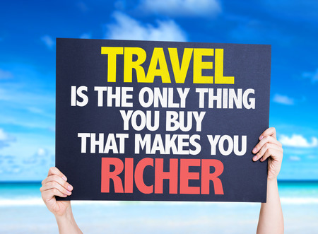cardboard only: Hands holding Travel is the Only Thing you Buy that Makes you Richer card with beach background Stock Photo