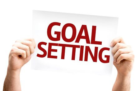 setting goals: Hands holding cardboard with text Goal Setting on white background Stock Photo