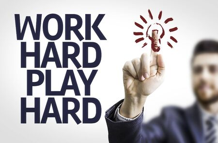 hard work: Business man pointing to transparent board with text: Work Hard Play Hard