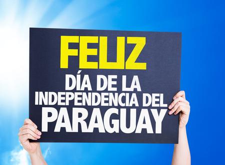 feliz: Hand holding cardboard with text Feliz on sky background Stock Photo