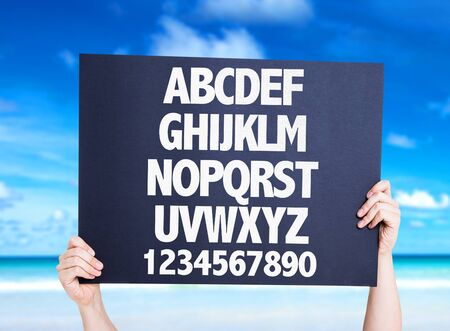 alphabetical: Hand holding cardboard with Alphabetical and Numerical text on sea background