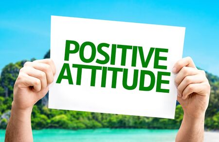 Mano que sostiene la cartulina con el texto de la actitud positiva en el fondo de la isla