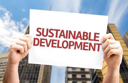 desarrollo sostenible: Mano que sostiene la cartulina con el texto de Desarrollo Sostenible en el fondo de la ciudad
