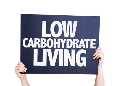 carbohydrate: Hand holding cardboard with text Low Carbohydrate Living on white background