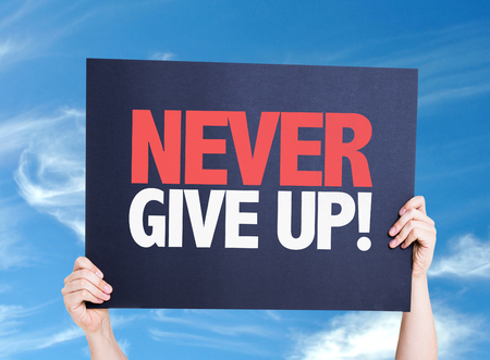 give up: Hand holding cardboard with text Never Give Up on sky background