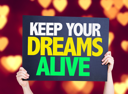 keep your hands: Hand holding cardboard with text Keep Your Dreams Alive on heart bokeh background