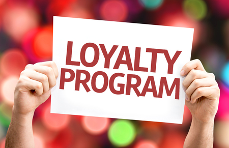 Hands holding cardboard with text Loyalty Program on bokeh background