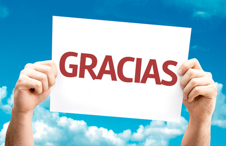 gratefulness: Hands holding Thank You (in Spanish) card with sky background Stock Photo