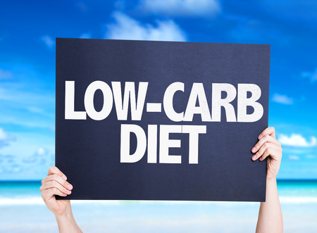Hands holding Cardboard Low Carb Diet text on beach background