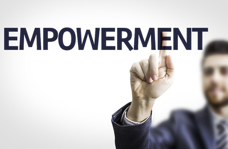 supervise: Business man pointing to transparent board with text: Empowerment Stock Photo