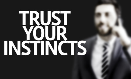 instincts: Business man with the text Trust your Instincts in a concept image
