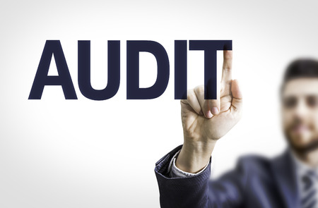 conformance: Business man pointing to transparent board with text: Audit