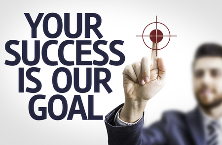 our: Business man pointing to transparent board with text: Your Success Is Our Goal Stock Photo