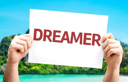 Hands holding Dreamer card with island background