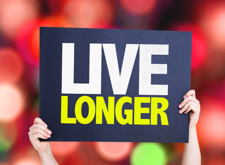longer: Hands holding Live Longer card with bokeh background Stock Photo