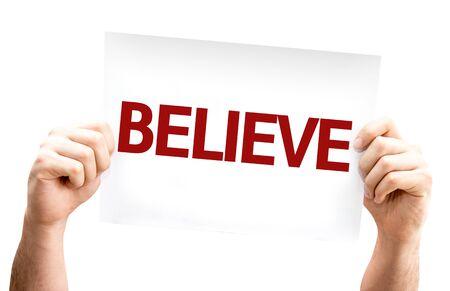 creer: Manos que sostienen la tarjeta de Believe aislado en blanco