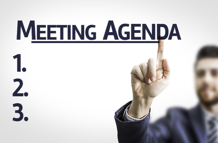 meeting agenda: Business man pointing to transparent board with text: Meeting Agenda Stock Photo