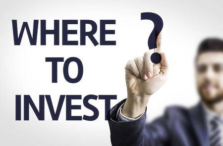 where: Business man pointing to transparent board with text: Where to Invest? Stock Photo