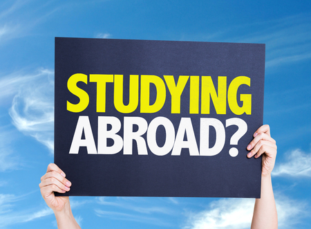 student travel: Hands holding cardboard with text Studying Abroad on sky background