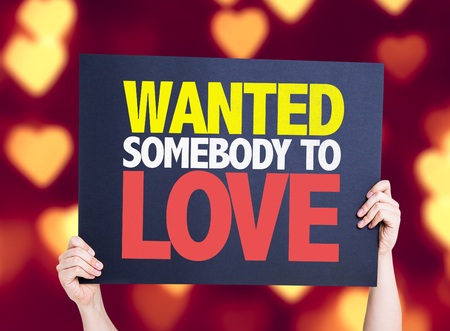 somebody: Hands holding Wanted Somebody to Love card with heart bokeh background