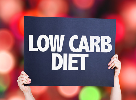 low carb diet: Hands holding cardboard with Low Carb Diet text on bokeh background