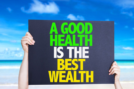 wealth: Hands holding cardboard with text A Good Health Is The Best Wealth with beach background Stock Photo