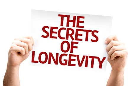 longevity: Hands holding cardboard with text The Secrets of Longevity isolated on white background Stock Photo