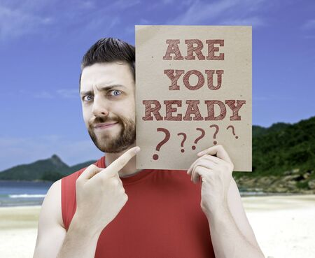 man holding card: Man holding card with text Are You Ready on beach background