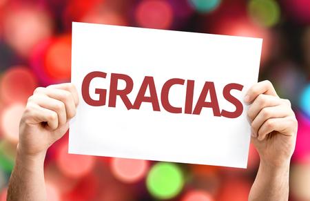 agradecimiento: Manos que sostienen Gracias (en espa�ol) tarjeta con fondo de colores con las luces desenfocado Foto de archivo